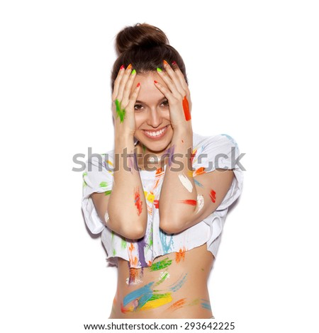 Young cheerful soiled in paint girl having fun. Smiling Woman with bright makeup and hairstyle covering her face with her hands on White background not isolated - stock photo