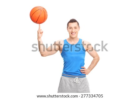 Young cheerful sportsman spinning a basketball on his finger and looking at the camera isolated on white background - stock photo