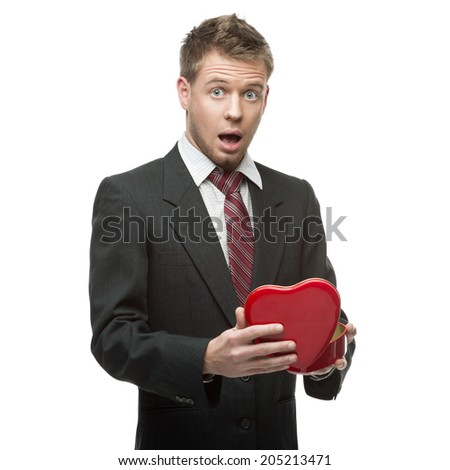 young cheerful surprised caucasian businessman in black suit holding red opened box in form of heart