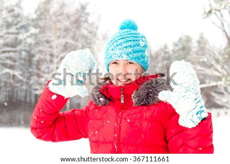 Young cheerful teenage girl showing blue snowy gloves. Bright outdoors horizontal image. - stock photo