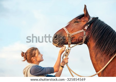 Young cheerful teenage girl stroking big chestnut horse's nose. Vibrant multicolored summertime outdoors horizontal image with filter - stock photo