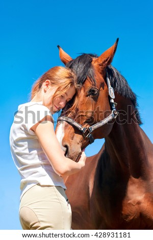 Young cheerful teenage girl tender embracing her big lovely horse. Vibrant multicolored summertime outdoors vertical image. - stock photo