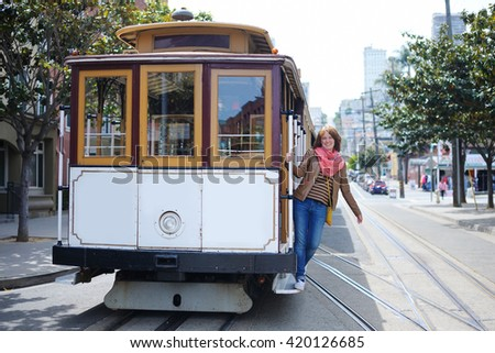 Young cheerful tourist taking a ride in famous cable car in San Francisco, California, USA - stock photo