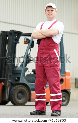 young cheerful warehouse worker driver in uniform in front of forklift stacker loader - stock photo