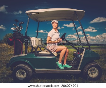 Young cheerful woman driving golf cart  - stock photo