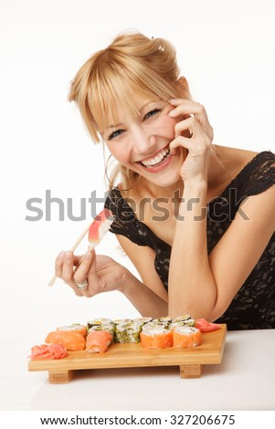 Young cheerful woman eating sushi with chopsticks - stock photo