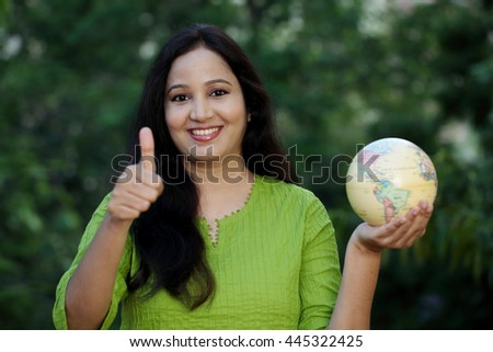 Young cheerful woman giving  thumb up gesture, holding globe against green background - stock photo