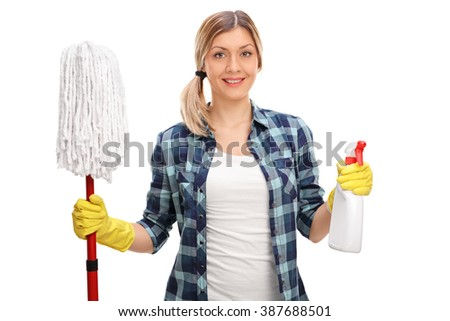 Young cheerful woman holding a mop and a spray bottle isolated on white background