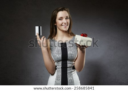 Young cheerful woman holding credit card and gift box - stock photo