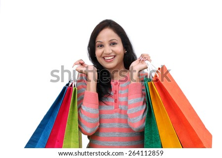 Young cheerful woman holding shopping bags - stock photo