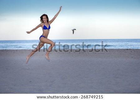Young cheerful woman in bikini jumping on the beach.  - stock photo