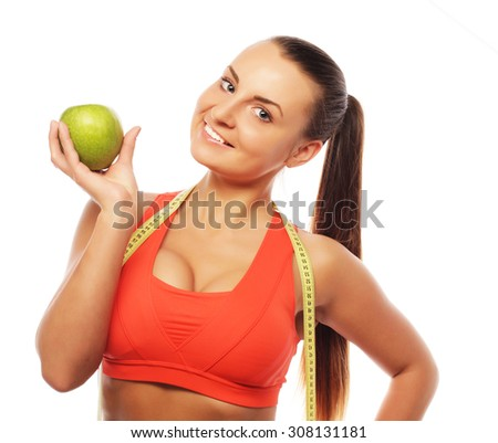 Young cheerful woman in sports wear with apple, isolated over white background - stock photo