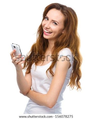 Young cheerful woman is pleased by incoming message on her phone, isolated over white - stock photo