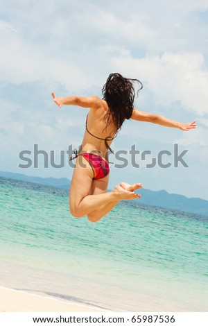 Young cheerful woman jumping on beach - stock photo