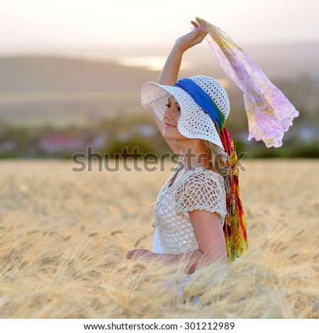 young cheerful woman on golden cereal field in summer - stock photo