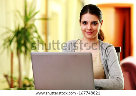 Young cheerful woman sitting at the table with laptop at home