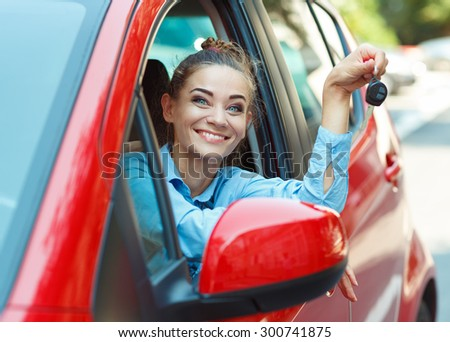Young cheerful woman sitting in a car with keys in hand - concept Rent a car - stock photo