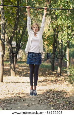 Young cheerful woman smiling and hanging by the bar in a park with selective focus - stock photo