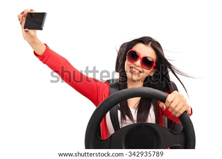 Young cheerful woman taking a selfie while driving a car isolated on white background - stock photo