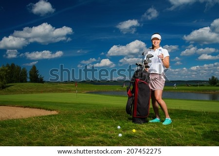 Young cheerful woman with bag and bottle of water on a golf field - stock photo