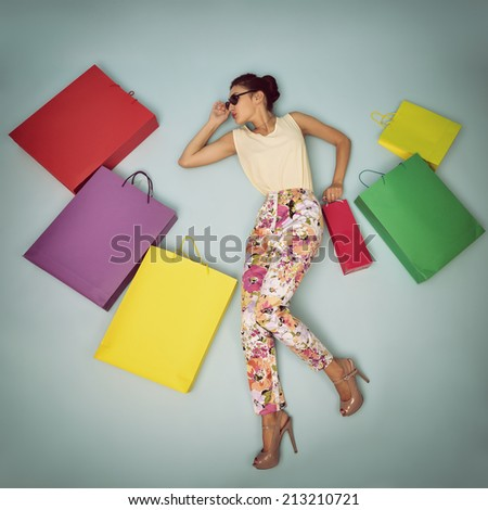 Young cheerful woman with colored paper shopping bags. Shopaholic. Shopping concept and ideas. Urban lifestyle. Image filtered. - stock photo