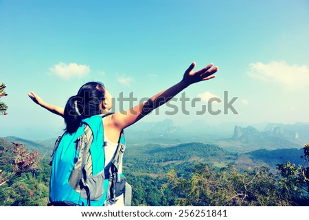 young cheering woman hiker open arms at mountain peak - stock photo