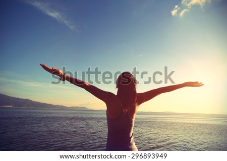 young cheering woman jogger open arms at sunrise seaside,vintage effect - stock photo