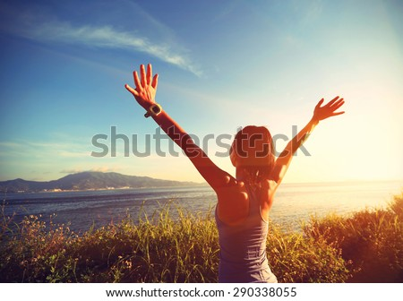 young cheering woman open arms at sunrise seaside - stock photo