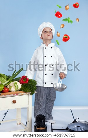 Young chef and his juggling with vegetables in a pan - stock photo
