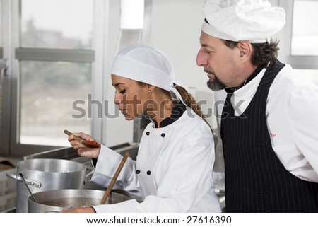 young chef and mature chef tasting tomato sauce. - stock photo