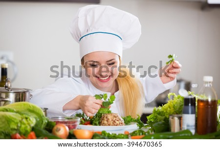 Young chef arranging vegetables on plate with cheese in kitchen