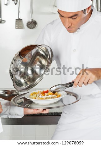 Young chef checking pasta dish with tong in commercial kitchen