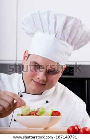 Young chef decorating delicious salad in kitchen - stock photo