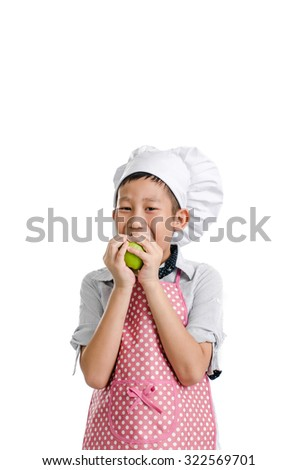Young chef eating green apple isolated on white. - stock photo