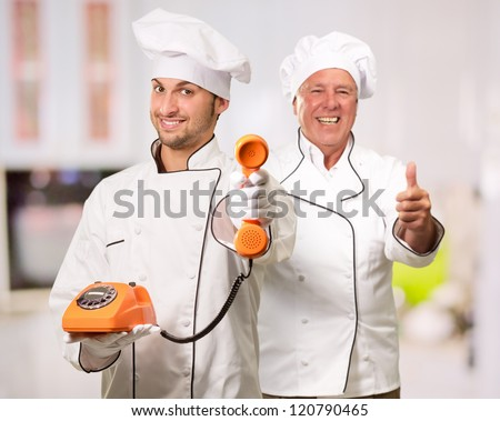 Young Chef Holding Telephone In Front Of Mature Chef, Indoor - stock photo