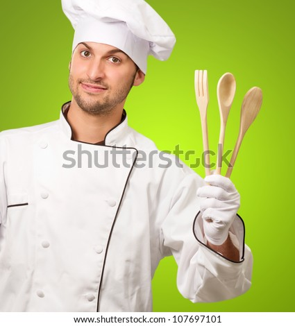 Young Chef Holding Wooden Spoon Isolated On Green Background - stock photo