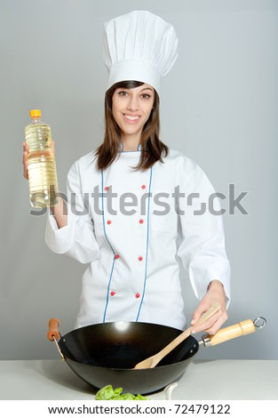 Young chef in a neutral background with a wok and a bottle of oil - stock photo