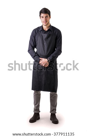 Young chef or waiter posing, wearing black apron and shirt isolated on white background - stock photo