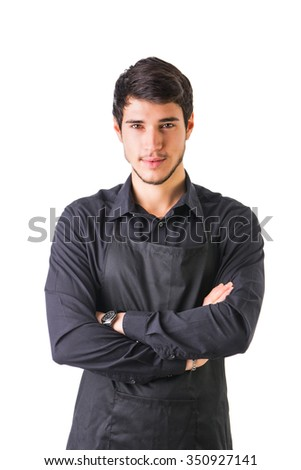 Young chef or waiter posing, wearing black apron and shirt isolated on white background, with arms crossed on his cheset - stock photo