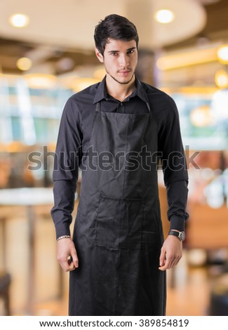 Young chef or waiter wearing black apron in restaurant - stock photo