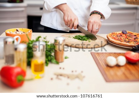 Young chef prepares a man in the kitchen - stock photo