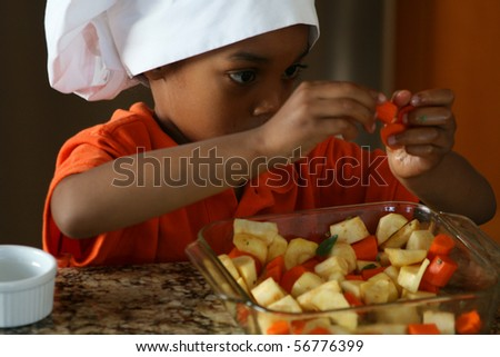Young chef prepares carrots and parsnips for the oven. - stock photo