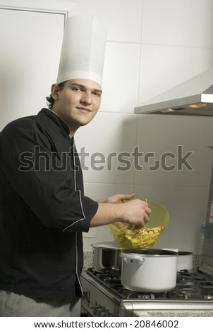 Young chef standing over a stove poring the contents from a bowl to a pot on the stove. Vertically framed photo.