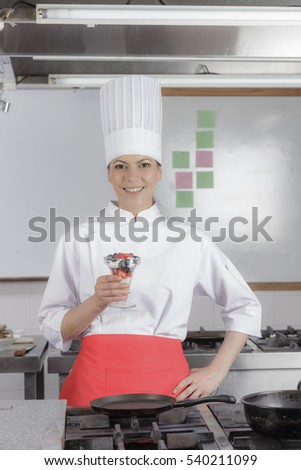 Young chef wearing white and carrying deserts in industrial hotel kitchen