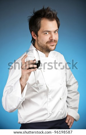 Young chef with glass of wine agaist blue background