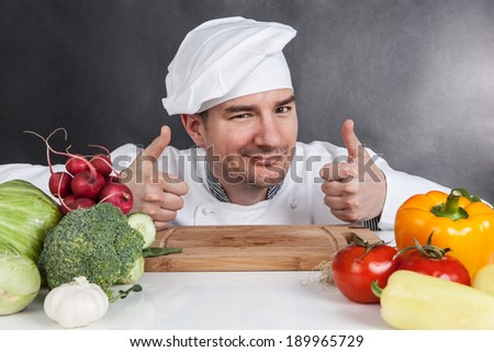 Young chef with OK sign and vegetable on black background - stock photo