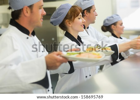Young chefs putting fish dishes on order station standing in a row - stock photo