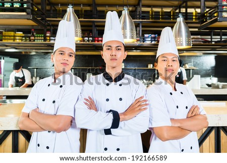 Young chefs standing with arms crossed - stock photo