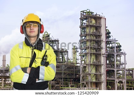 Young chemical engineer posing in front of a biodiesel refinary plant, wearing a hard hat, fire retardant clothing with reflective stripes, looking proudly into the camera - stock photo