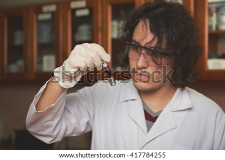 young chemist with colour liqiud in flask in lab - stock photo